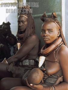 Himba mother breast-feeding her infant . Kaokoveld .  Namibia .